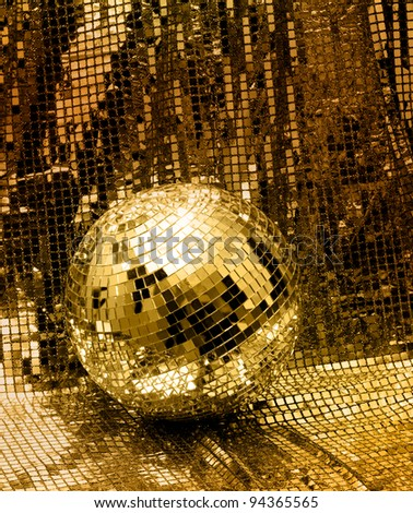 Golden disco mirror ball reflect light on glitter canvas background