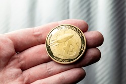 Golden Dogecoin token coin in a caucasian male hand