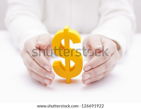 Golden dollar symbol protected by hands
