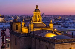 Golden Dome - A dusk view of illuminated dome and bell tower at the top of the 16th-century Renaissance style Iglesia de la Anunciación - The Annunciation Church in Seville, Andalusia, Spain.