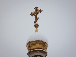 Golden dome with a cross in the snow