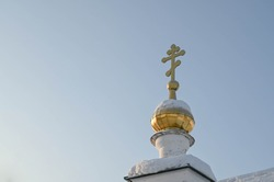 Golden Dome with cross of the Russian Orthodox Church. Blue sky at sunny winter day. Snow on dome.