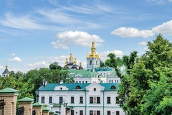 golden domes and a cross of the Orthodox Church against the blue sky, on a warm summer day Ukraine, Kiev