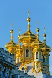 Golden domes of a Christian Church in Tsarskoye Selo on the background of blue sky