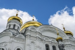 Golden domes of the ancient majestic church on Belaya Gora (Perm Territory, Russia) against a blue sky with lush white clouds. Antique patterned masonry walls, arched windows. close-up bottom view