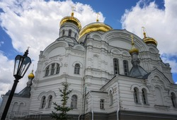Golden domes of the ancient majestic church on Belaya Gora (Perm Territory, Russia) against a blue sky with lush white clouds. close-up bottom view. Antique patterned masonry walls, arched windows.