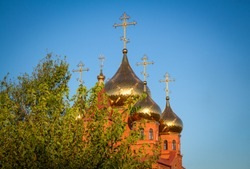 Golden domes of the church against the sky.