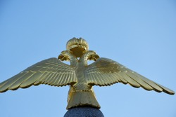 Golden double-headed eagle is placed on a concrete stand, against the background of bright blue sky.