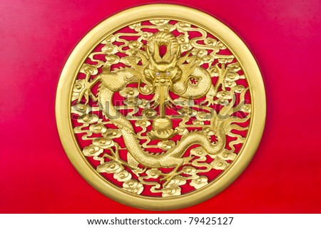 Golden dragon(Chinese: Long) wood carving in Red background. In china, Traditional dragon(long) symbol of imperial power, dignity, harmonious, solidarity, lucky and successful.
