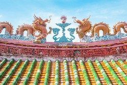 Golden dragon statue on Shrine roof, twin dragon statue on chinese temple roof as asian art, golden dragon with blue sky background, Thauland. Twin dragon on chinese temple roof and bamboo tiles roof
