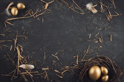 Golden Easter eggs in nest with hay on dark black slate table background.