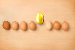 Golden egg standout from the roll of eggs on wood table, Find the Golden Eggs Concept