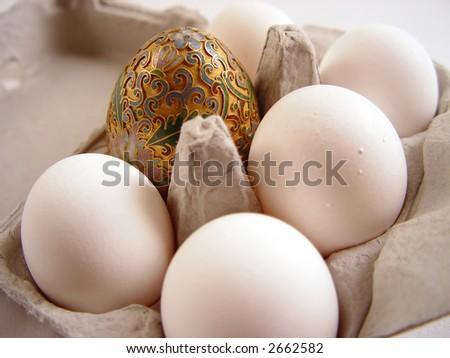 Golden egg with half dozen white cage free  eggs. - stock photo