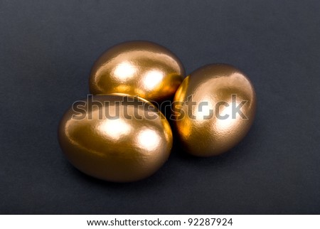 Golden eggs. A symbol of making money and successful investment on black background