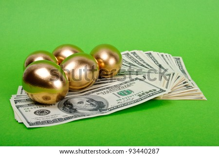 Golden eggs. A symbol of making money and successful investment on green background