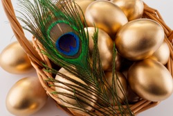 Golden eggs in a basket on a white background, close-up, decorated with a peacock feather. The concept of Easter, luxury, a symbol of abundance and wealth.