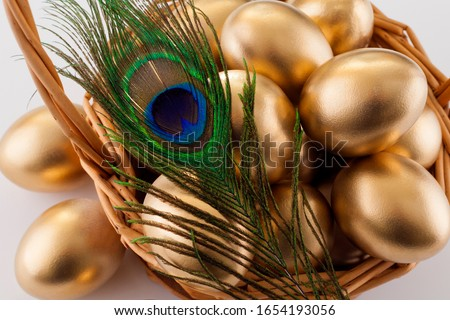 Golden eggs in a basket on a white background, close-up, decorated with a peacock feather. The concept of Easter, luxury, a symbol of abundance and wealth. Stock photo ©