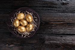 Golden eggs in a nest on dark wooden background