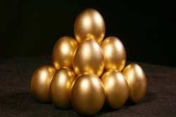 Golden eggs on black background. A pyramid of golden eggs