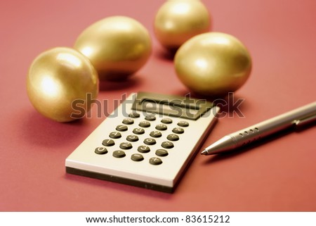 Golden Eggs with Calculator and Pen on Red Background
