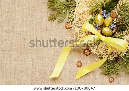 Golden eggs with floral arrangement on a canvas background