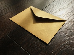Golden envelope on wooden background, news and communication concept