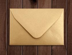 Golden envelope over wooden table.