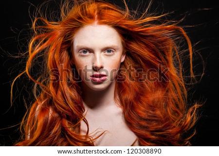Golden Fashion Girl Portrait.Wavy Red Hair. Black Background