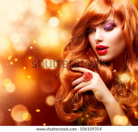 Golden Fashion Girl Portrait.Wavy Red Hair. Gold Blinking Background.Holiday