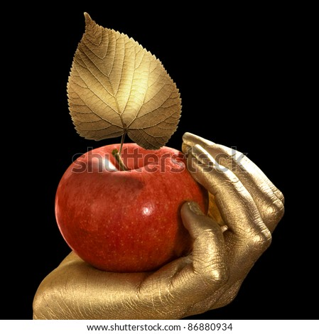 golden feminine hand holding a perfect red apple with golden leaf,Studio shot in black back - stock photo