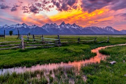Golden Fiery Sunset at Grand Teton - A colorful spring sunset at Teton Range, seen from an abandoned old ranch in Mormon Row historic district, in Grand Teton National Park, Wyoming, USA.
