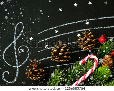 Golden fir cones, fir branches, Christmas decor on the stave with treble clef. Holiday background. #1256583754