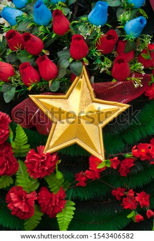 Golden five-pointed star. Five-pointed star of gold color in a wreath of flowers #1543406582
