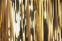 Golden foil tinsel strips. Festive decoration background