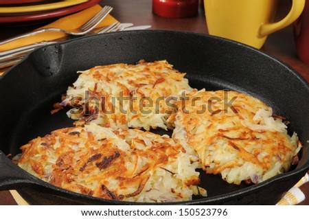 Golden fried latkes in a cast iron skillet near serving plates