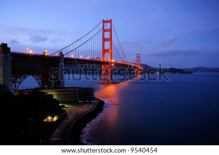 Golden Gate Bridge and Fort Point overlook glow in the dusk after a winter storm - landscape orientation.