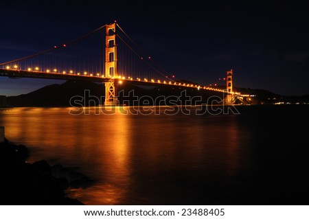 Golden Gate Bridge as seen from Fort Point overlook is glowing in the night against starry sky