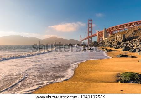 Golden Gate Bridge at sunset seen from beach, San Francisco, California.