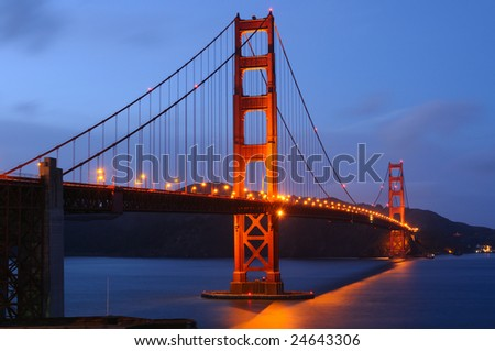 Golden Gate Bridge glows after a spring storm. Shot at dusk from Fort Point viewpoint. Landscape (horizontal) orientation.