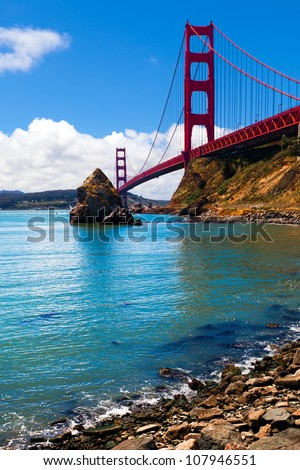 Golden Gate Bridge. Great view from the water's edge near the foot of the bridge. Bright sunny day.