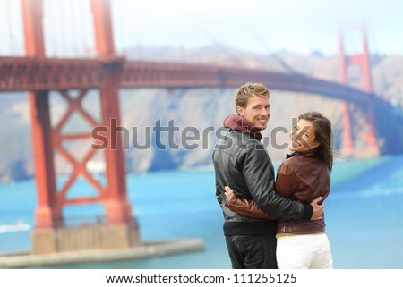 Golden gate bridge happy travel couple in San Francisco, USA smiling at camera. Young interracial hipster couple enjoying the view at the famous travel landmark.