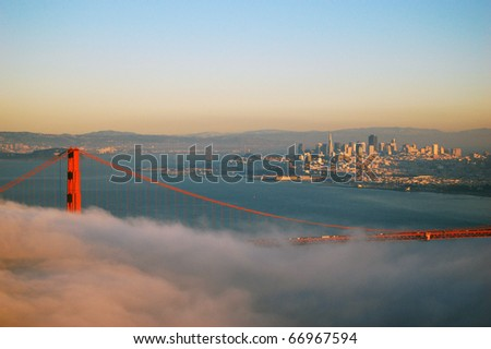 Golden Gate Bridge in fog in a winter dusk, with San Fransisco in the back ground.