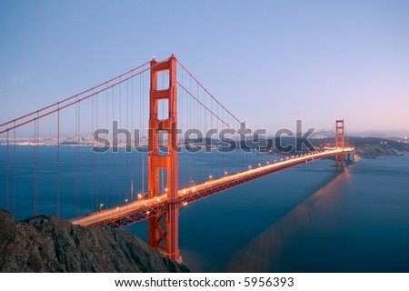 Golden Gate Bridge is glowing on the clear fall evening with San Francisco skyline, Bay Bridge and Twin Peaks TV Tower in the background. - stock photo