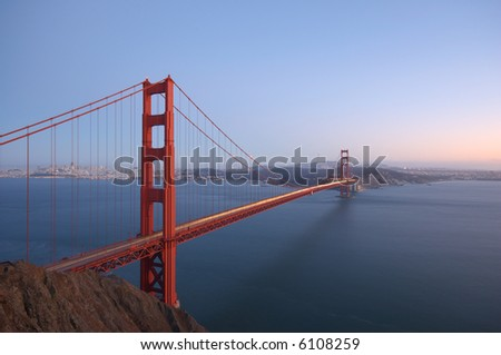 Golden Gate Bridge is glowing on the clear fall evening with San Francisco skyline, Bay Bridge and Twin Peaks TV Tower in the background.