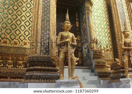Golden giant statues guarding massive door to Phra Mondop at Wat Phra Kaew temple in Bangkok, Thailand.