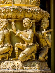 Golden giants sculpture carrying temple pillar at Wat Sri Pan Ton, Nan, Thailand: The temple with golden sanctuary is a beautiful architecture chapel.