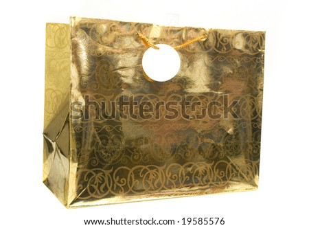 golden gift bag with tag isolated against white background