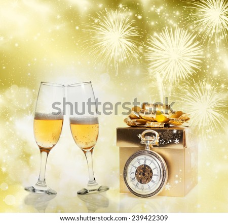 Golden gift box, champagne glasses and clock close to midnight on sparkling holiday background