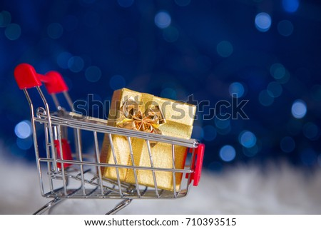Golden gift box in small supermarket trolley with garland lights on blue bokeh background. New year banner with empty space. Concept of Xmas shopping. #710393515