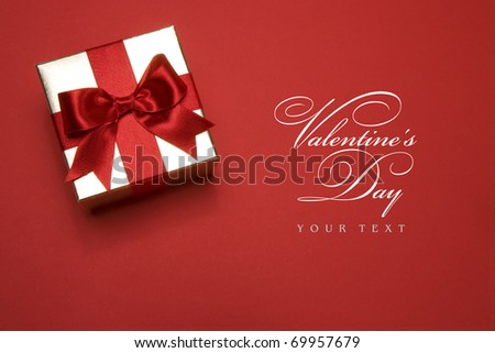 golden gift box with a red bow on red background